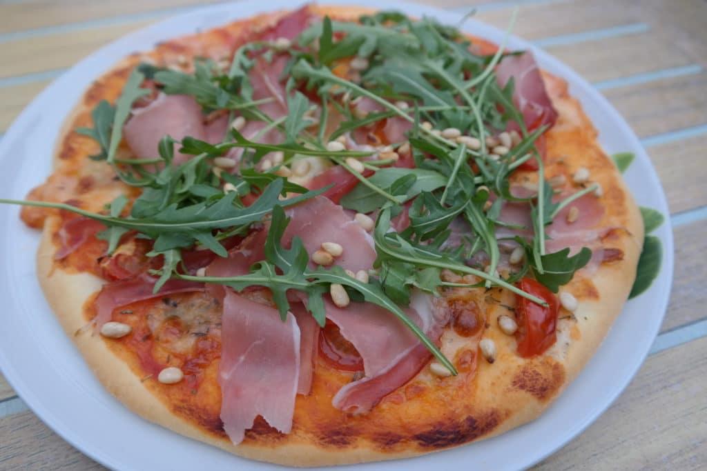 Pizza mit Rucola, Parmaschinken und Zedernkernen